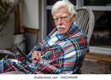 Senior man reading a book on his e-book reader when sitting in the rocking chair.  Portrait of a happy, retired man reading a book on his device.