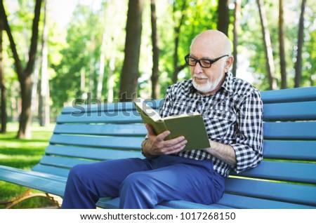 5fca297e7134e Senior man reading book outdoors. Elderly casual man in eyeglasses having  rest on the bench