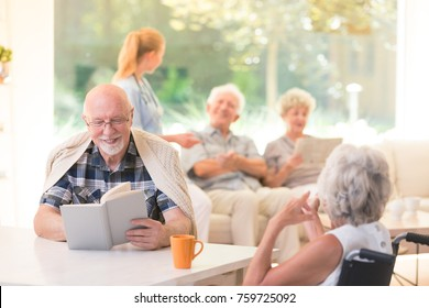 Senior man reading a book and smiling while sitting with a friend at a table in nursing house