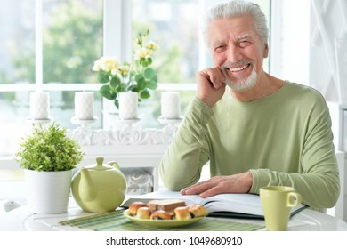 Senior man  reading book while drinking tea