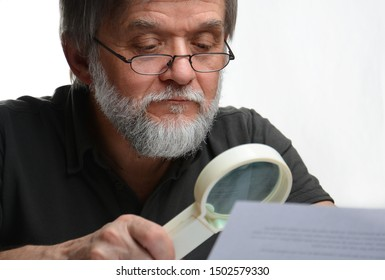 Senior man is reading a contract with loupe