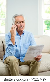 Senior man reading document while talking on phone in living room at home