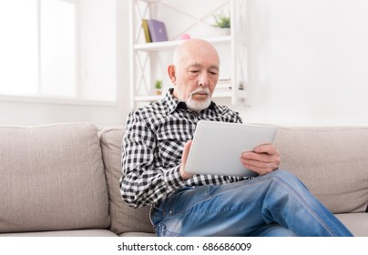 Senior man reading news on digital tablet. Surprised mature male using portable computer at home
