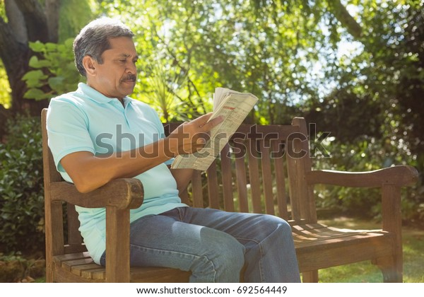 Senior man reading  newspaper in the garden