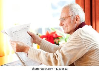 Senior man reading a newspaper at home