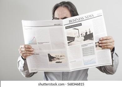Senior man reading newspaper on gray background