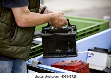 A senior man recycling a car battery