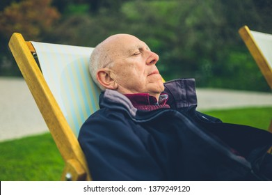 A senior man is relaxing in a deck chair outdoors