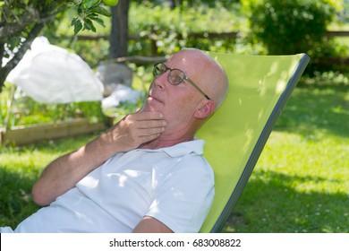 Senior man relaxing in the deckchair in his garden, summer time