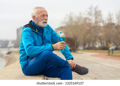 Senior man resting and drinking water after workout