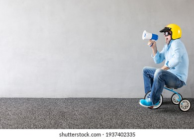 Senior man riding children bicycle. Full length portrait of funny businessman against concrete wall with copy space. Business start up concept