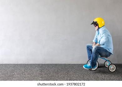 Hombre mayor montando bicicletas para niños. Retrato de largo y largo de un divertido hombre de negocios contra una pared de hormigón con espacio para copiar. Concepto de inicio de negocio