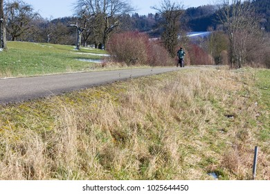 senior man with rollator on a bikeway and sunny winter day with blue sky in south germany