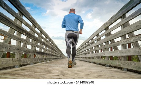 senior man is running on a long trestle over Long Pine Creek -  recreational Cowboy Trail in northern Nebraska