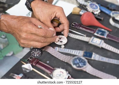 Senior Man 's hand is holding a small screw driver to repairing piece of wristwatch, the work is very precise, Hard and Precision Work Concept.