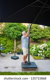Senior man setting up beach parasol in his garden on a sunny day