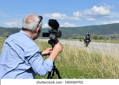 Senior man shooting video of motorcycle racing with his digital camera on tripod. Amateur motor race on the former airport runway near the town of Dupnitsa, Bulgaria