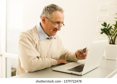 senior man shopping internet using his laptop in the room