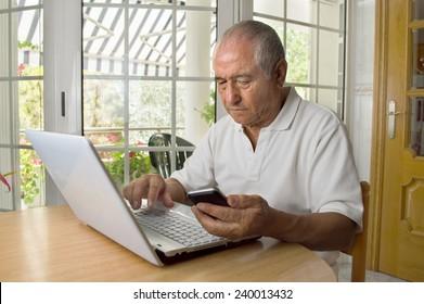 senior man shopping internet using his laptop in the room