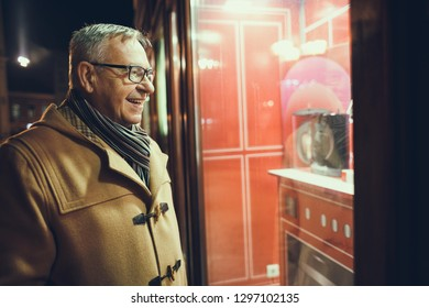 Senior man is shopping and looking at store front.