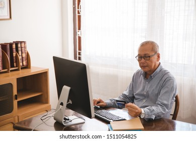 Senior man shopping online using computer and credit card.
