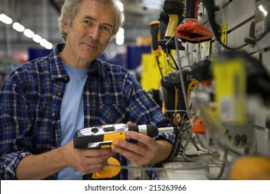 Senior man shopping for power drill in DIY shop, smiling, portrait