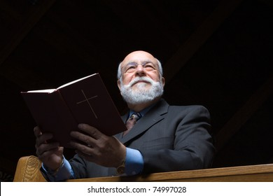 Senior man shot from below holding a hymnal in church pew.