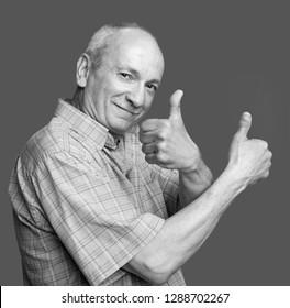 Senior man showing ok sign on blue background