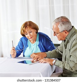 Senior man showing old woman in nursing home a tablet computer