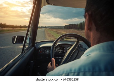 Senior man sits in a car on a rural empty road with red fuel lamp appeared on the dashboard