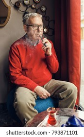 Senior man is sitting in cafe and smoking electronic cigarette.