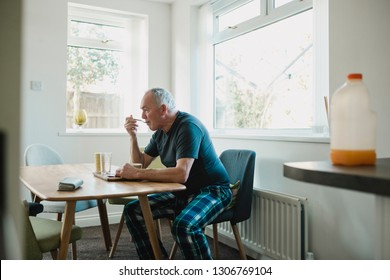 Senior man is sitting at the dining table in his home, enjoying a bowl of porridge for breakfast.