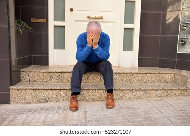 senior man sitting at the doorway house crying because he is evicted from his home
