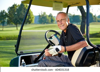 Senior man sitting in a golf cart on the green