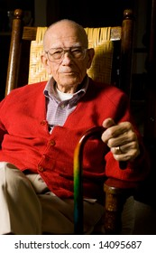 Senior Man Sitting with hands on Cane.