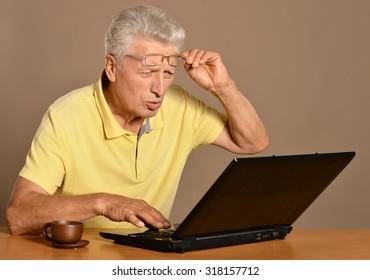 Senior man sitting with laptop on table
