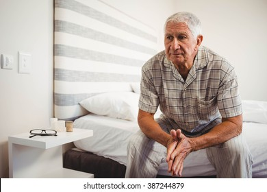 Senior man sitting on bed in bedroom