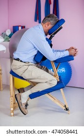 Senior man sitting on massage chair in clinic