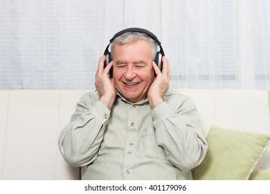 Senior man sitting on  sofa with headphones  and enjoys listening music.Senior man  listening music