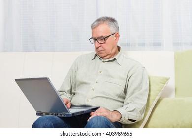 Senior man sitting on sofa and using laptop.Senior man using laptop