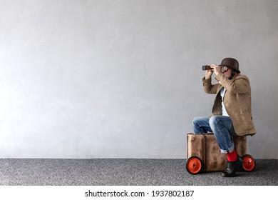 Senior Mann sitzend auf Vintage Koffer. Vollständiges Portrait von lustigen Geschäftsleuten auf Betonmauer mit Kopienraum. Unternehmensgründungskonzept
