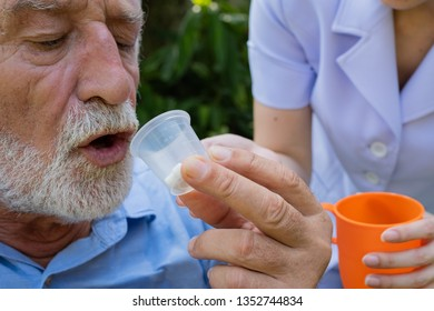 senior man sitting on wheelchair and eating medecine with nurse, takes care and discussion and cheer in the garden at nursing home, give a medecine for health care