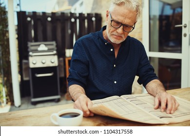 Senior man sitting at a patio table and looking unhappy while reading the financial pages in a newspaper and drinking a cup of coffee