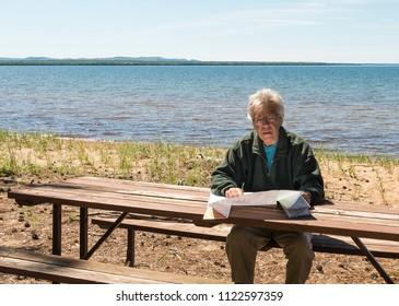 Senior man sitting at the picnic table and examining a map