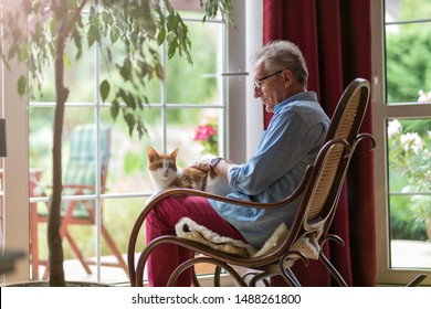 Senior man sitting in a rocking chair with his cat in his lap