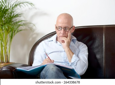 a senior man sitting in a sofa taking notes