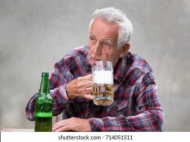 Senior man sitting at table and drinking beer from mug