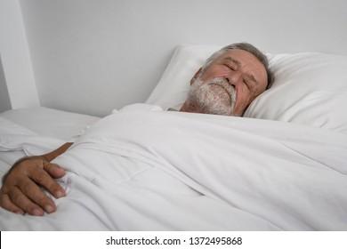 senior man sleeping alone on bed in room