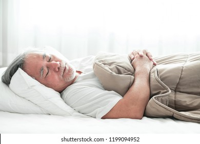 Senior man sleeping in bed. Old asian man sleeping comfortably in bed with curtain open. Senior lifesyle concept.
