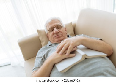 Senior man sleeping on sofa with a book